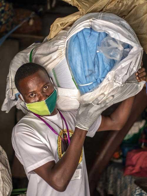 L'agente Jean Kinhouande distribuisce zanzariere nel distretto di Agla di Cotonou, in Benin, per combattere la malaria nonostante l'interruzione della pandemia di COVID-19. (Foto di Yanick Folly/AFP via Getty Images, 28 aprile 2020)