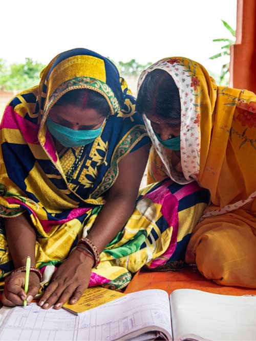 Roona and Veena Devi (L–R), members of a self-help group organized by Jeevika, at work during an SHG meeting in Gurmia, Bihar, India. (August 28, 2021)