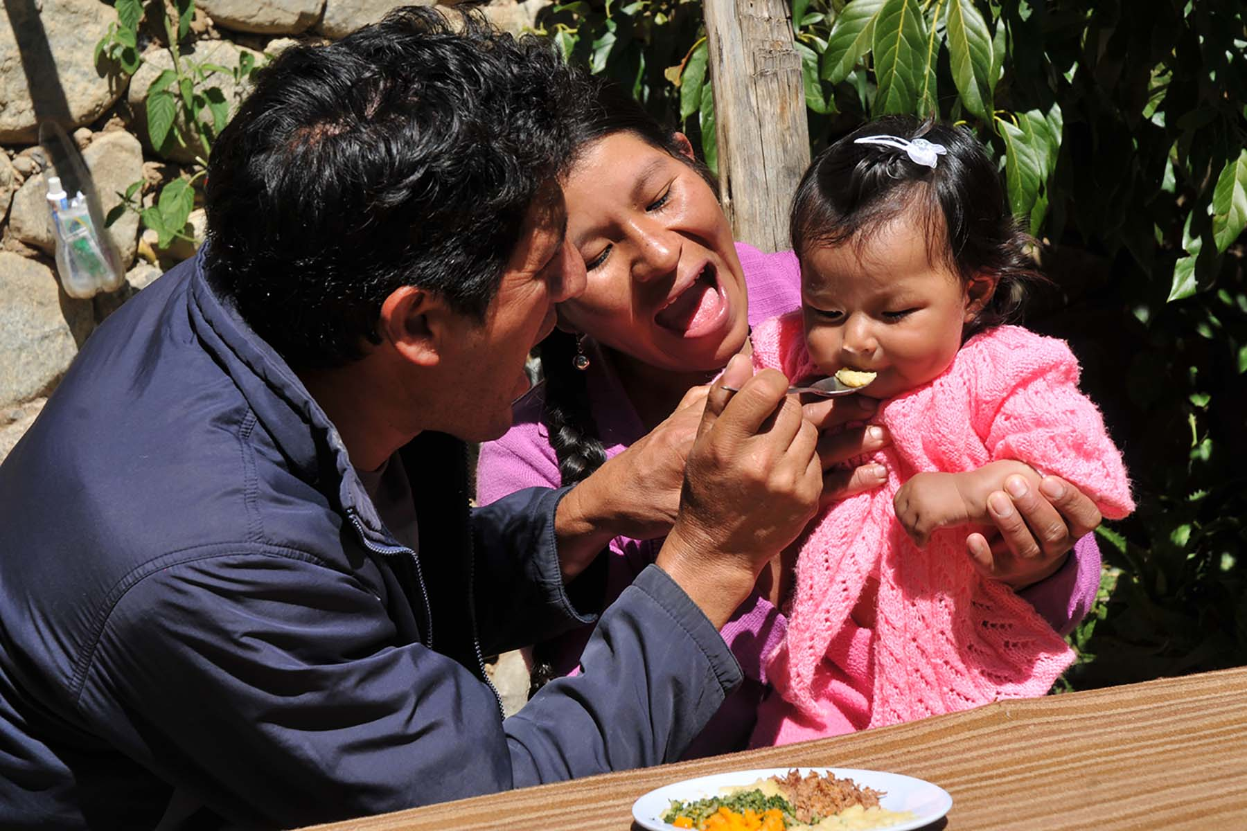 Picture of a father and mother feeding their child in one of Peru's nutrition projects.