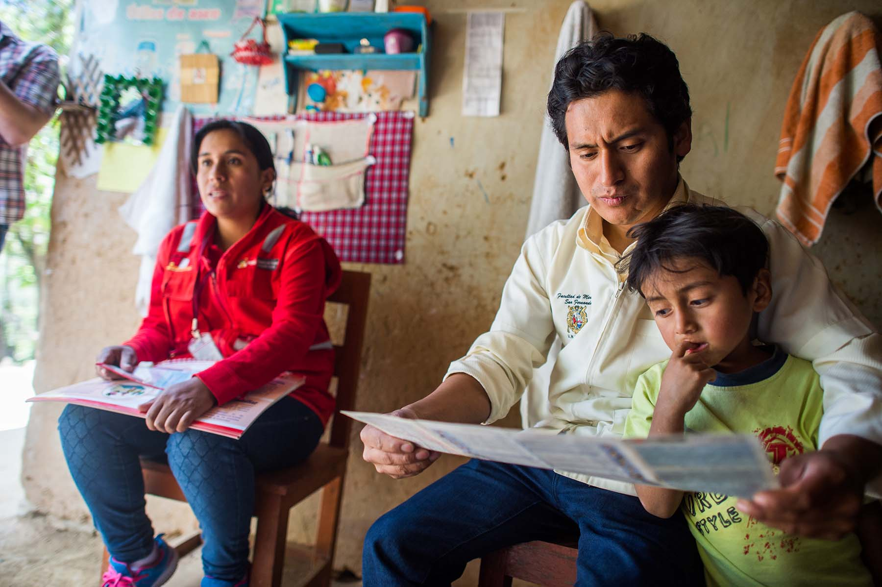 Picture of health care workers review the growth chart of a child while speaking to a mother during a home visit. (Sogobamba, Peru) P
