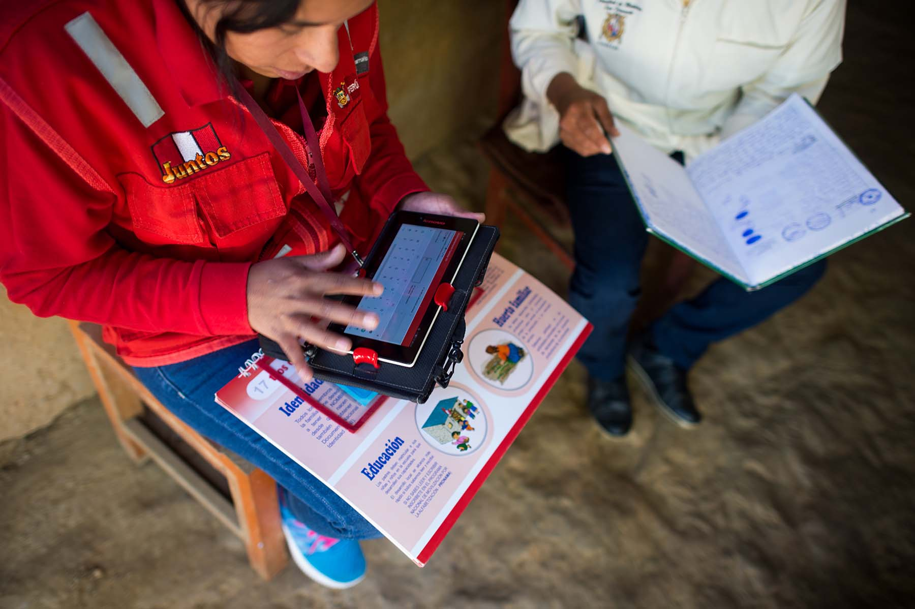 Picture of health care workers use a tablet to collect health and development data while speaking to a mother about her son during a check-in visit. (Sogobamba, Peru)