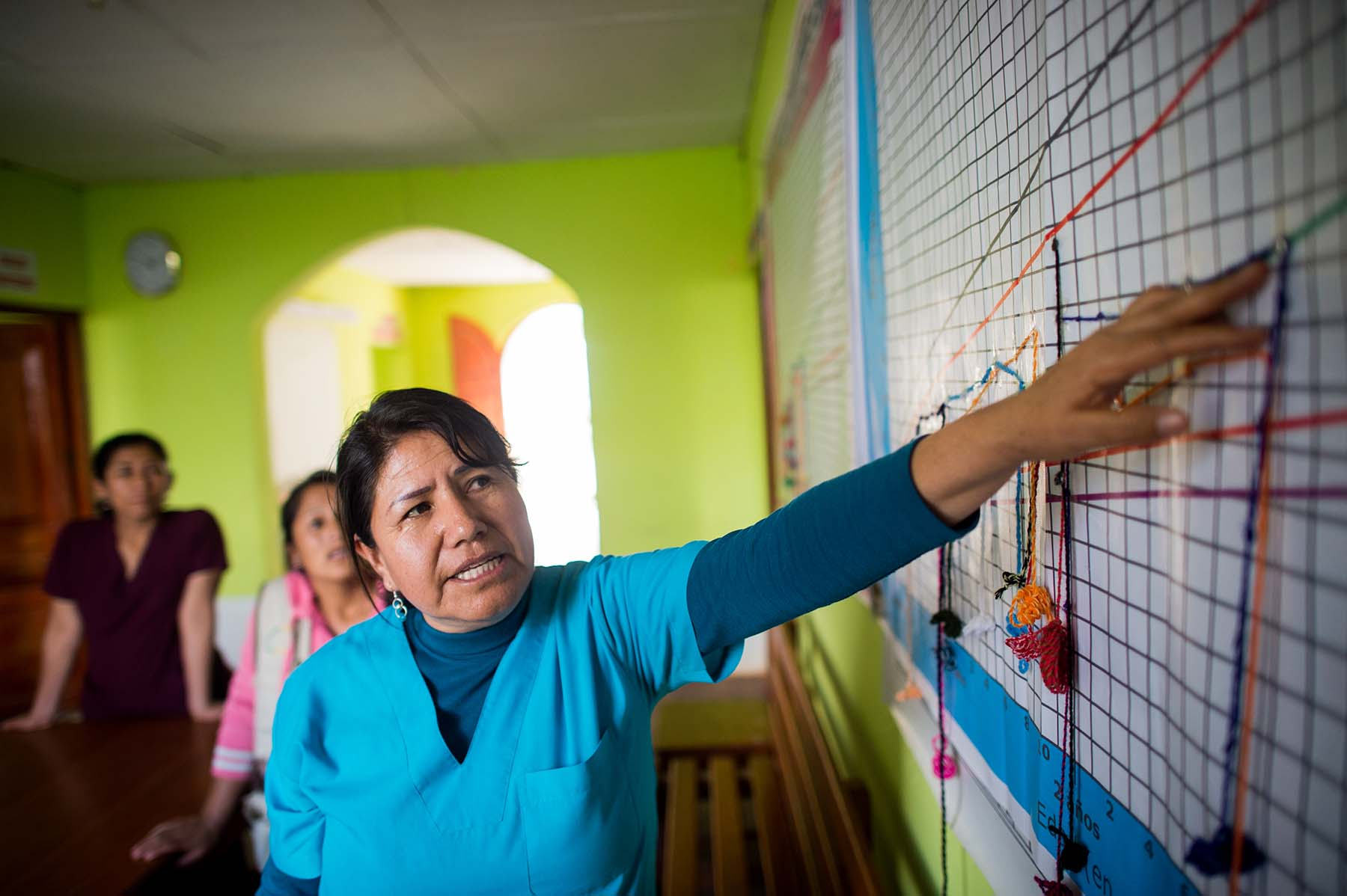Picture of a health care worker explains a children's growth chart at a local maternal and child community center where health workers track interventions and weight of each child under 3. (Sogobamba, Peru)