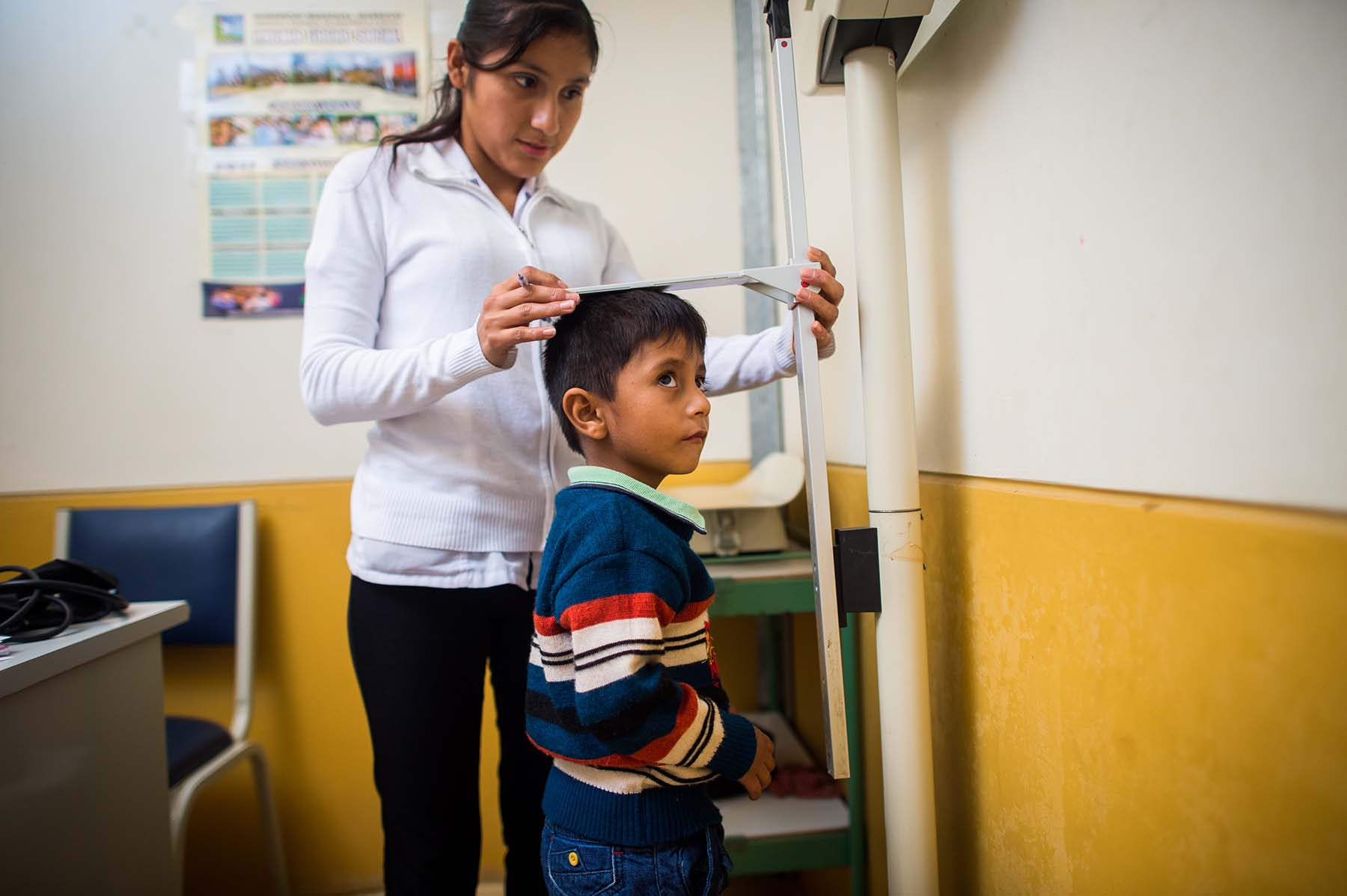 Picture of a nurse measures the height of a boy at a health clinic during a regular checkup. (Acomayo, Peru)