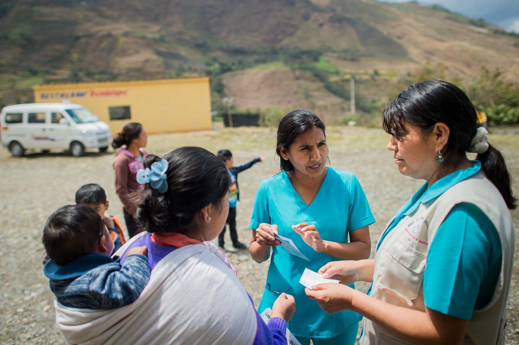 Picture of nurses from a local health program counsel a mother on how best to care for her young children. (Acomayo, Peru)