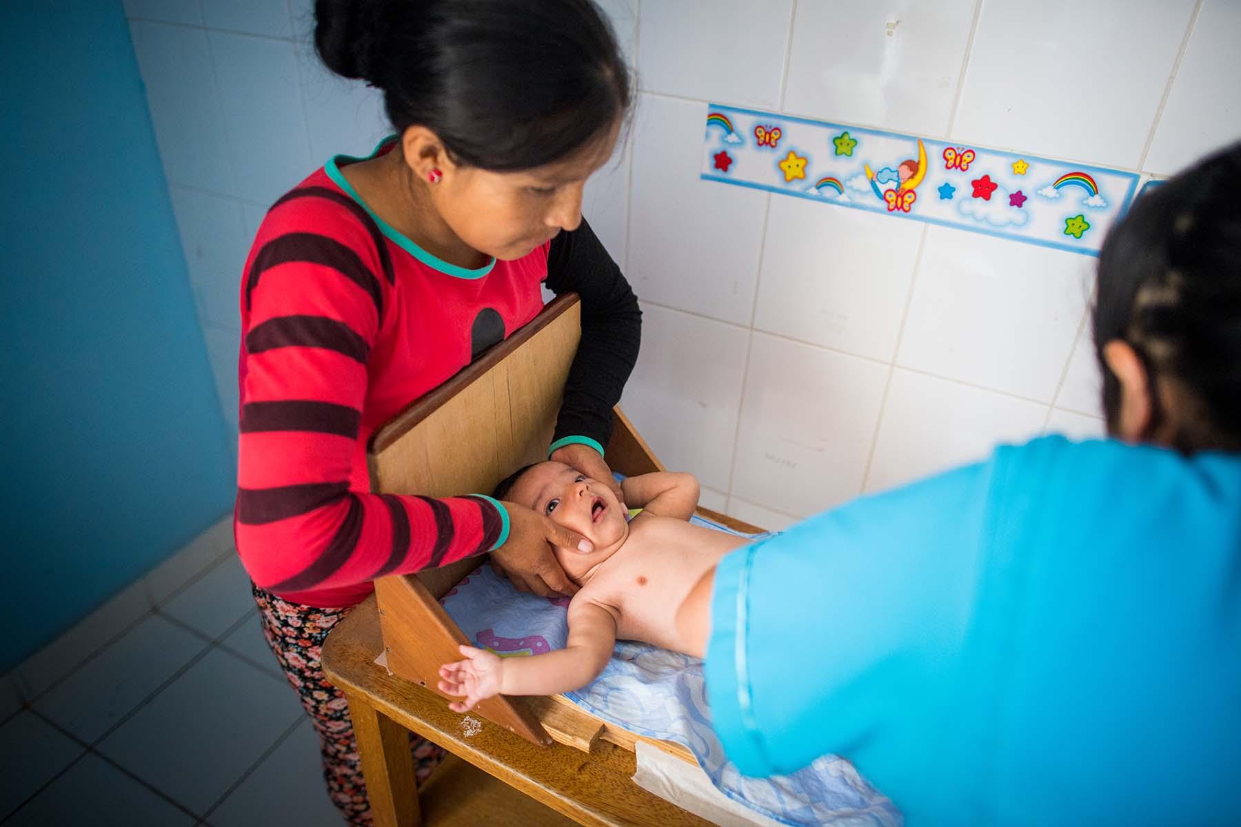 照片中一位母亲在当地卫生所抱着她正在量身高的婴儿。(秘鲁,Potracanch)